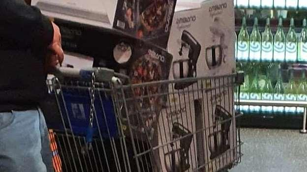 Photo of man in Aldi with six Special Buy Stand Mixers in Trolley, man facing away from camera close image of hand and leg visible