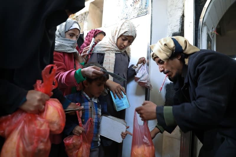 A woman and children receive food donations from a charity kitchen in Sanaa