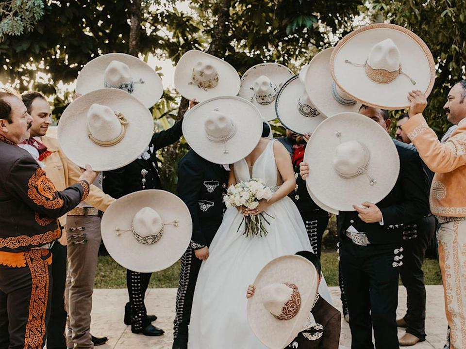A bride and groom lean together while groomsmen dressed as Charros cover them with sombreros.
