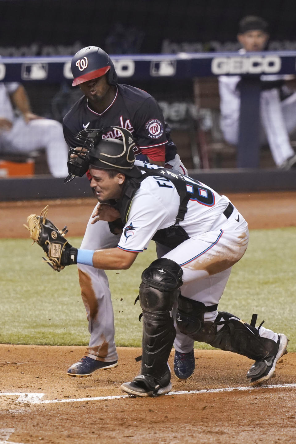 Washington Nationals' Alcides Escobar collides with Miami Marlins catcher Nick Fortes (84) during the sixth inning of a baseball game, Tuesday, Sept. 21, 2021, in Miami. Escobar scored on the play. (AP Photo/Marta Lavandier)