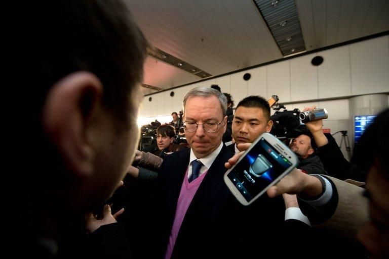 Google chairman Eric Schmidt (C) is surrounded by the media after arriving at Beijing airport, on January 10, 2013