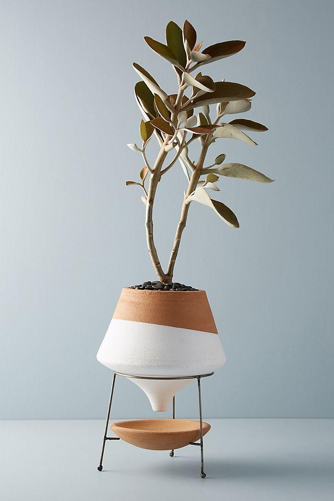 """The tapered funnel and suspended construction add a little drama to this home accent. $58, Anthropologie. <a href=""""https://www.anthropologie.com/shop/dipped-clay-pot-stand"""" rel=""""nofollow noopener"""" target=""""_blank"""" data-ylk=""""slk:Get it now!"""" class=""""link rapid-noclick-resp"""">Get it now!</a>"""