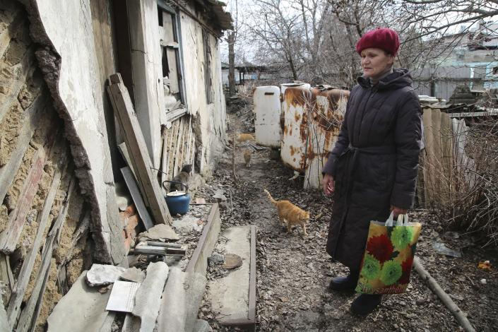 FILE - In this April 9, 2021, file photo, a woman visits her home in the separatist-controlled territory to collect her belongings after a recent shelling near a frontline outside Donetsk, eastern Ukraine. Tensions are rising over the conflict in eastern Ukraine, with growing violations of a cease-fire and a massive Russian military buildup near its border with the region. (AP Photo, File)