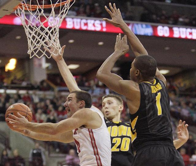 Ohio State's Aaron Craft, left, tries to shoot the ball past Iowa's Jarrod Uthoff, center, and Gabriel Olaseni during the second half of an NCAA college basketball game on Sunday, Jan. 12, 2014, in Columbus, Ohio. Iowa won 84-74. (AP Photo/Jay LaPrete)