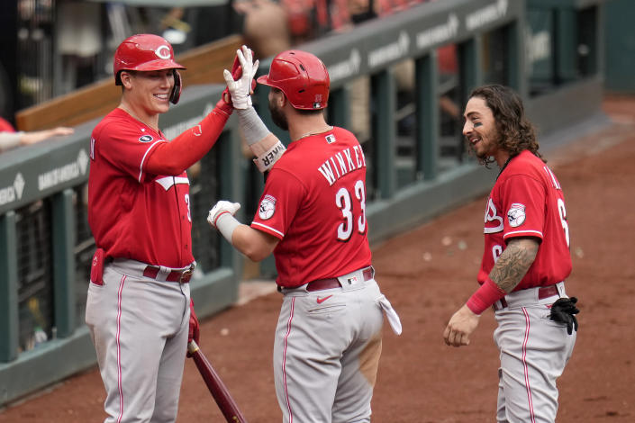 Cincinnati Reds' Jesse Winker (33) is congratulated by teammates Jonathan India, right, and Tyler Stephenson, left, after hitting his third home run of a baseball game during the ninth against the St. Louis Cardinals Sunday, June 6, 2021, in St. Louis. (AP Photo/Jeff Roberson)