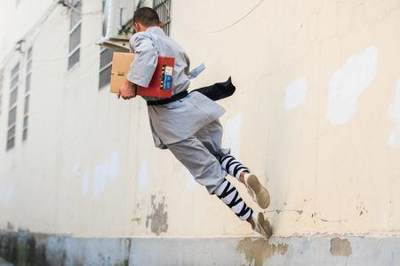 A man dressed in a kung fu costume displays his martial arts skills as he delivers a parcel for Alibaba's logistics company Cainiao, ahead of the Singles Day shopping festival, in Dengfeng, Henan province, China October 31, 2018. Picture taken October 31, 2018.  REUTERS/Stringer