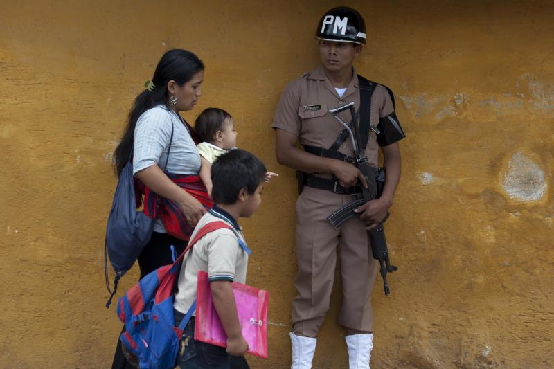 A family walks past a soldier standing guard at the Hotel Casa Santo Domingo, the venue of the 43rd General Assembly of the Organization of American States, OAS, in Antigua Guatemala, Guatemala, Tuesday, June 4, 2013. Counternarcotics and counterterrorism strategy, as well as human rights throughout the Western Hemisphere, are expected to be main topics of discussion. (AP Photo/Moises Castillo)