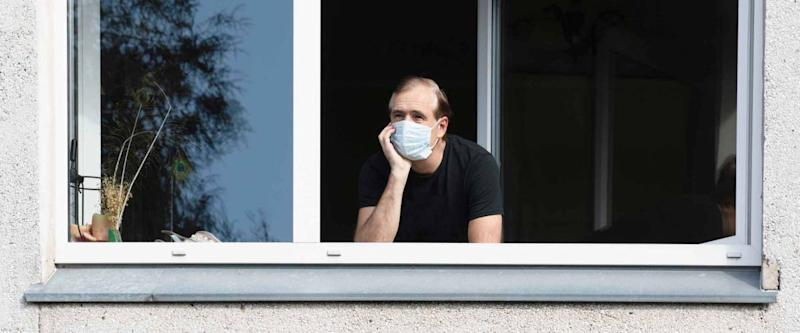 Man in medical face mask looking through window.