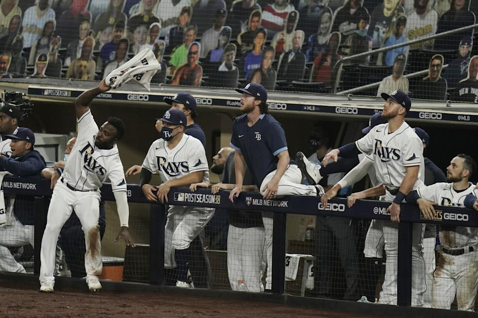Tampa Bay Rays players react to a sacrifice fly.