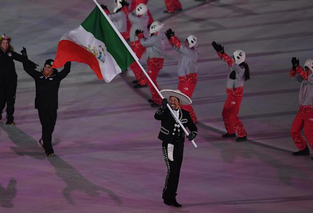Flag bearer German Madrazo of Mexico leads the team during the Opening Ceremony wearing a traditional Mexican sombrero. (Note the panda hats in the background.) (Photo: Harry How/Getty Images)