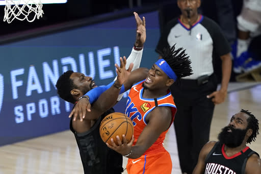Oklahoma City Thunder's Luguentz Dort, center, goes up for a shot as Houston Rockets' Jeff Green, left, defends during the second half of an NBA basketball first round playoff game Saturday, Aug. 29, 2020, in Lake Buena Vista, Fla. (AP Photo/Ashley Landis)