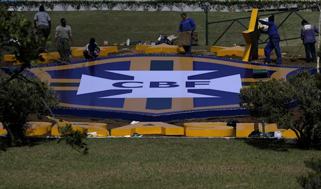 Workers install the logo of Brazil's Soccer Confederation (CBF) at the Granja Comary training centre, where Brazil soccer squad will start its preparation to Russia 2018 World Cup, in Teresopolis, Brazil May 18, 2018. REUTERS/Ricardo Moraes