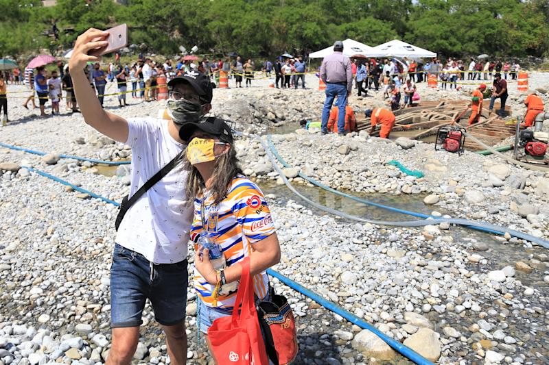 MONTERREY, MEXICO - AUGUST 05: A couple take a selfie during a visit to pray for the recently unearthed sculpture of the Virigin of Guadalupe at Santa Catarina river on August 5, 2020 in Monterrey, Mexico. At least 400 people went to Santa Catarina river to take stones and water after tropical storm Hanna unearthed sculpture of the Virgin of Guadalupe. (Photo by Medios y Media/Getty Images)