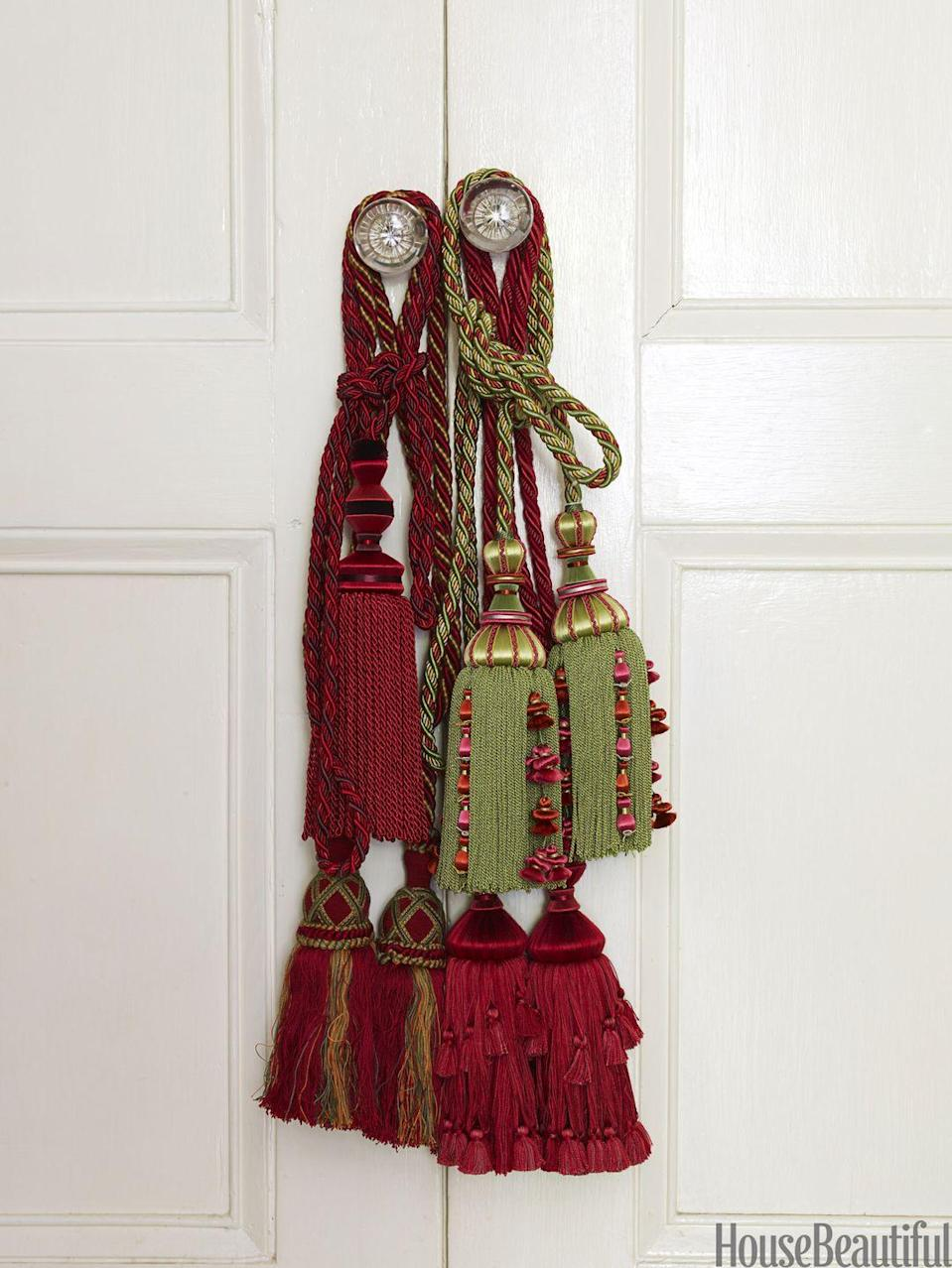 <p>Hang red and green tassels on your doors, desk, and chest of drawers. They're a finishing touch that's totally budget-friendly. </p>