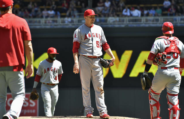 Los Angeles Angels pitcher Trevor Cahill, center, waits to be pulled by manager Brad Ausmus, left, after giving up a walk to Minnesota Twins' C.J. Cron in the fifth inning of a baseball game Wednesday, May 15, 2019, in Minneapolis. (AP Photo/Jim Mone)