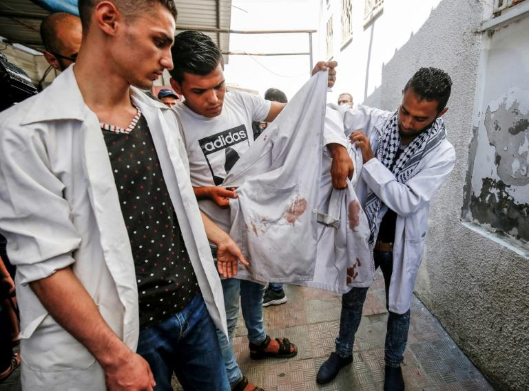 Colleagues of killed 21-year-old Palestinian volunteer medic Abdullah al-Qatati hold up his blood-stained white cloak during his funeral in the Gaza Strip on August 11, 2018, a day after he was killed during protests along the Israel-Gaza border