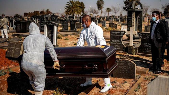 Relatives observe undertakers moving a casket containing the remains of a COVID-19 coronavirus patient during a funeral at the Avalon cemetery in Soweto, on July 24, 2020.