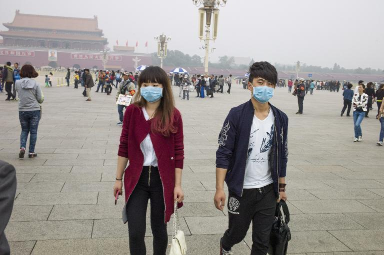 A couple wear face masks as they walk on Tiananmen Square in Beijing on October 11, 2014 after days of heavy smog