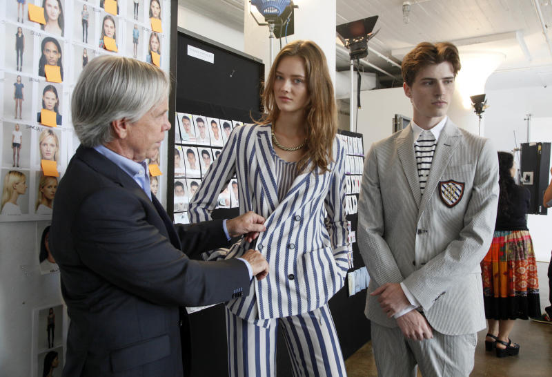 Designer Tommy Hilfiger works with models wearing two designs from his Spring 2013 collection, in New York, Wednesday, Sept. 5, 2012. Spring styles make their debut on catwalks around New York for eight days, starting Thursday. New York kicks off the seasonal previews for editors, stylists and retailers, who will later head to London, Milan and Paris. (AP Photo/Richard Drew)
