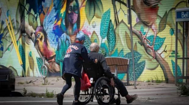 Someone in a mask helps push another masked person in a wheelchair in central Ottawa on Thursday. (Brian Morris/CBC - image credit)
