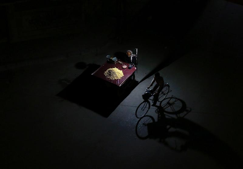 A Syrian man rides his bicycle past a man selling grain during a halt in fighting in Douma, east of Damascus, on February 29, 2016 (AFP Photo/Sameer Al-Doumy)