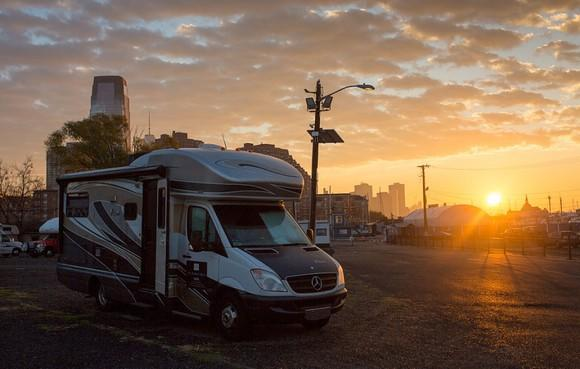 A Winnebago RV parked with a sunset in the background