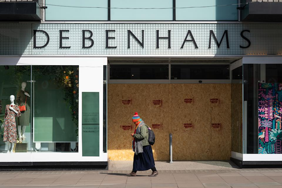A person walks past a boarded up Debenhams, Oxford Street, London as the UK continues in lockdown to help curb the spread of the coronavirus.