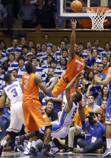 Duke's Rodney Hood (5) draws a charge from Syracuse's C.J. Fair (5) as Syracuse's Jerami Grant (3) and Duke's Tyler Thornton (3) stand near late in the second half of an NCAA college basketball game in Durham, N.C., Saturday, Feb. 22, 2014. Duke won 66-60. (AP Photo/Gerry Broome)