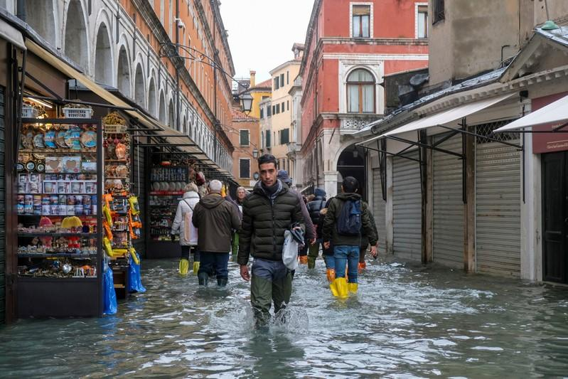 People walk in the flooded street during a period of seasonal high water in Venice