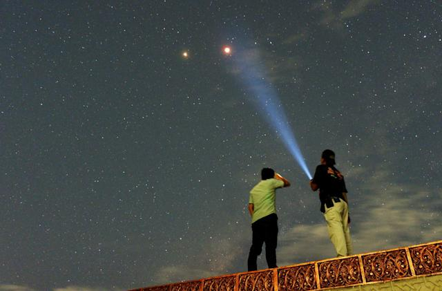 <p>Residents look at Mars alongside the lunar eclipse in Padang, Sumatra island, Indonesia, July 28, 2018. (Photo: Antara Foto/Iggoy el Fitra/via Reuters) </p>