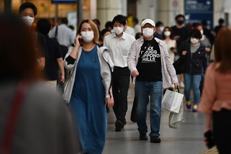 People wearing face masks walk in a train station amid the COVID-19 coronavirus outbreak in Kawasaki on May 11, 2020. (Photo by CHARLY TRIBALLEAU / AFP) (Photo by CHARLY TRIBALLEAU/AFP via Getty Images)