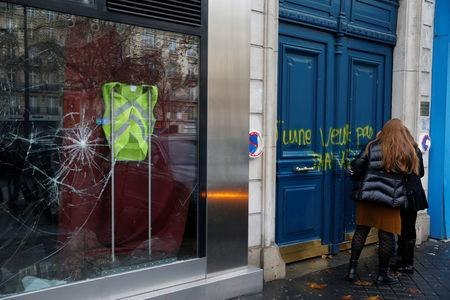 A yellow vest hangs inside a vandalized store the morning after clashes with protesters wearing yellow vests, a symbol of a French drivers' protest against higher diesel fuel taxes, in Paris, France, December 2, 2018.  REUTERS/Stephane Mahe
