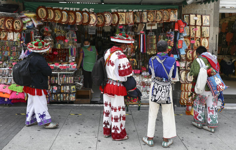 Huichol indigenous men observe religious images for sale outside the Basilica of Our Lady of Guadalupe in Mexico City, Monday, June 29, 2020. Mexico City is moving this week to the next stage of its gradual reopening from its COVID-19 pandemic lockdown. (AP Photo/Eduardo Verdugo)