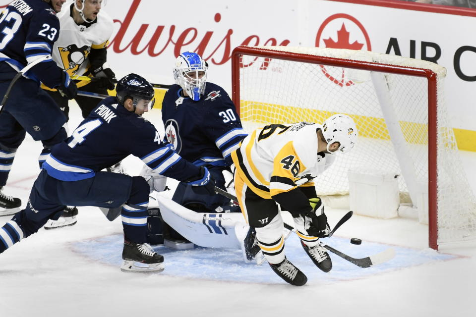 Pittsburgh Penguins' Zach Aston-Reese (46) scores against Winnipeg Jets goaltender Laurent Brossoit (30) during first-period NHL hockey game action in Winnipeg, Manitoba, Sunday, Oct. 13, 2019. (Fred Greenslade/The Canadian Press via AP)