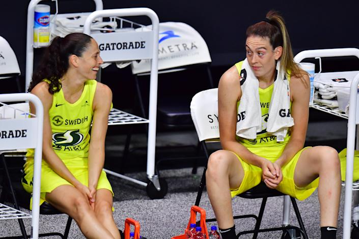 Sue Bird looks at Breanna Stewart, who has her eyebrows raised on the bench seats.