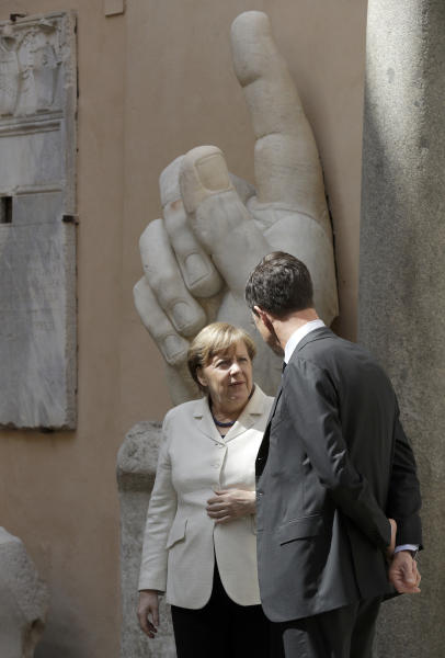 German Chancellor Angela Merkel, left, speaks with Dutch Prime Minister Mark Rutte after a group photo in the Cortile di Michelangelo during an EU summit in Rome on Saturday, March 25, 2017. EU leaders were gathering in Rome to mark the 60th anniversary of their founding treaty and chart a way ahead following the decision of Britain to leave the 28-nation bloc. In the background the remaining marble right hand of the Colossus of Constantine (312-315 AD). (AP Photo/Andrew Medichini)