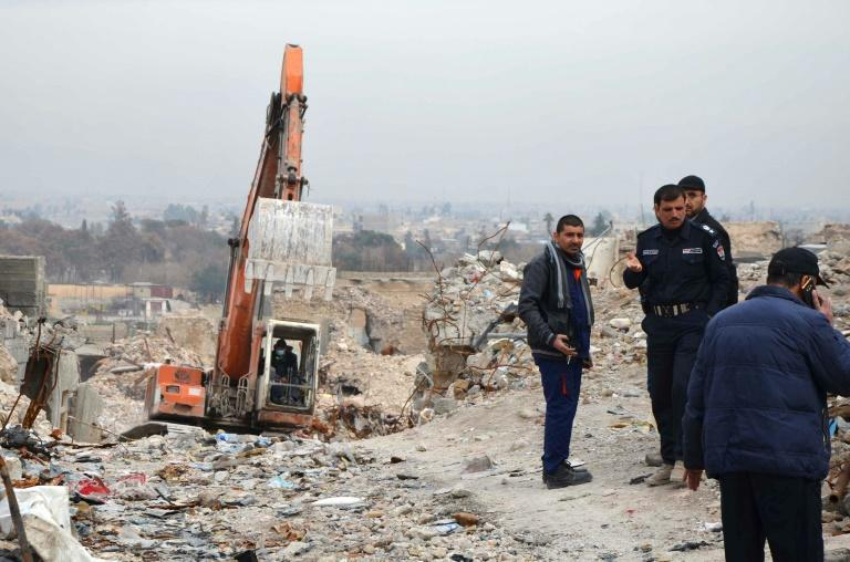 Iraqi men inspect a site in the city of Mosul where the rotting bodies of jihadists are believed to be found six months after their defeat