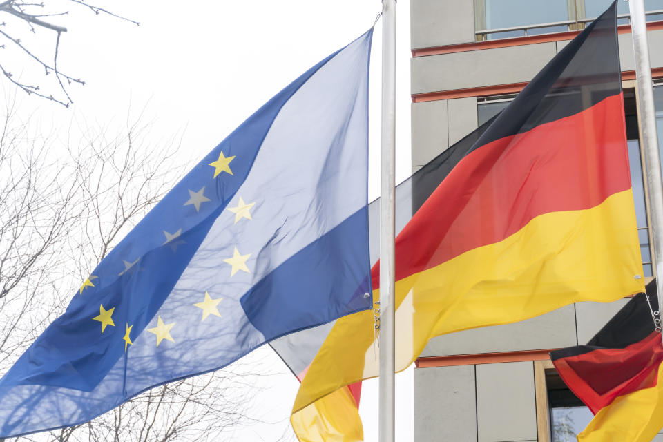 German and European Union flags waving against cloudy sky