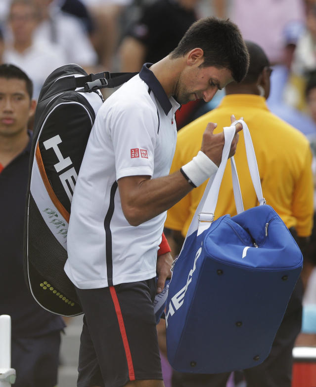 Serbia's Novak Djokovic walks off the court after the semifinal match against Spain's David Ferrer was postponed because of approaching inclement weather at the 2012 US Open tennis tournament, Saturday, Sept. 8, 2012, in New York. (AP Photo/Mike Groll)