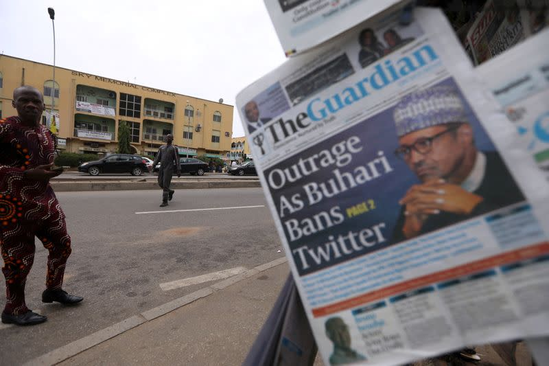 Man looks at newspapers at a newsstand in Abuja
