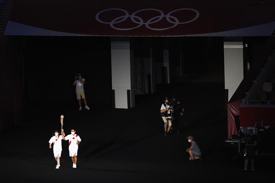 <p>TOKYO, JAPAN - JULY 23: The carrier of the torch makes their way to the Cauldron during the Opening Ceremony of the Tokyo 2020 Olympic Games at Olympic Stadium on July 23, 2021 in Tokyo, Japan. (Photo by Laurence Griffiths/Getty Images)</p>