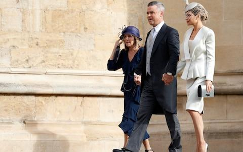 Robbie Williams arrives as his mother's hat is blown from her head - Credit: AFP