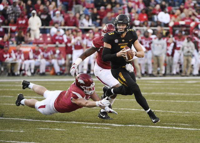 Missouri quarterback Drew Lock scrambles out of the pocket as he runs the ball against Arkansas during the second half of an NCAA college football game Friday, Nov. 24, 2017 in Fayetteville, Ark. (AP Photo/Michael Woods)