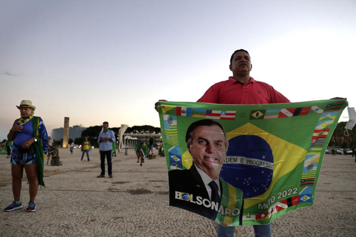 Demonstrators pray in support of Brazil's President Jair Bolsonaro in front of the Planalto presidential palace, in Brasilia, Brazil, Monday, March 29, 2021. President Bolsonaro has undertaken a cabinet reshuffle underscored by recent turmoil in his administration, and who has seen his approval ratings slide this year amid a raging new coronavirus pandemic that has taken the lives of more than 300,000 Brazilians. (AP Photo/Eraldo Peres)