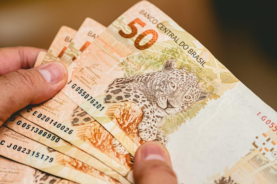 Real currency. Money from Brazil. Woman holding in hands a fifty Reais banknotes.