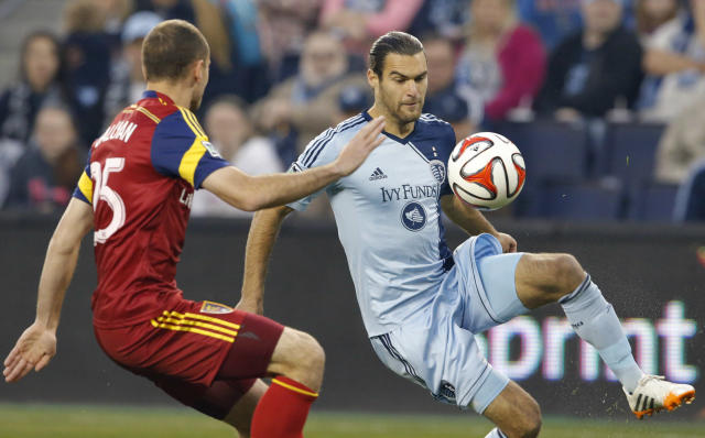 Sporting Kansas City midfielder Graham Zusi, right, plays the ball while covered by Real Salt Lake defender Rich Balchan (25) during the first half of an MLS soccer match in Kansas City, Kan., Saturday, April 5, 2014. (AP Photo/Orlin Wagner)