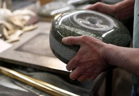 Kays Factory worker John Brown polishes granite by hand to make a curling stone in Mauchline, Scotland, Britain, January 11, 2018. REUTERS/Russell Cheyne