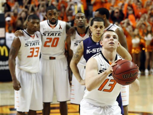 Oklahoma State's Marcus Smart (33), Michael Cobbins (20), Markel Brown (22), Brian Williams (4) and Kansas State's Angel Rodriguez watch as Oklahoma State's Phil Forte (13) takes a free throw in the second half of an NCAA college basketball game in Stillwater, Okla., Saturday, March 9, 2013. Oklahoma State won 76-70. (AP Photo/Sue Ogrocki)