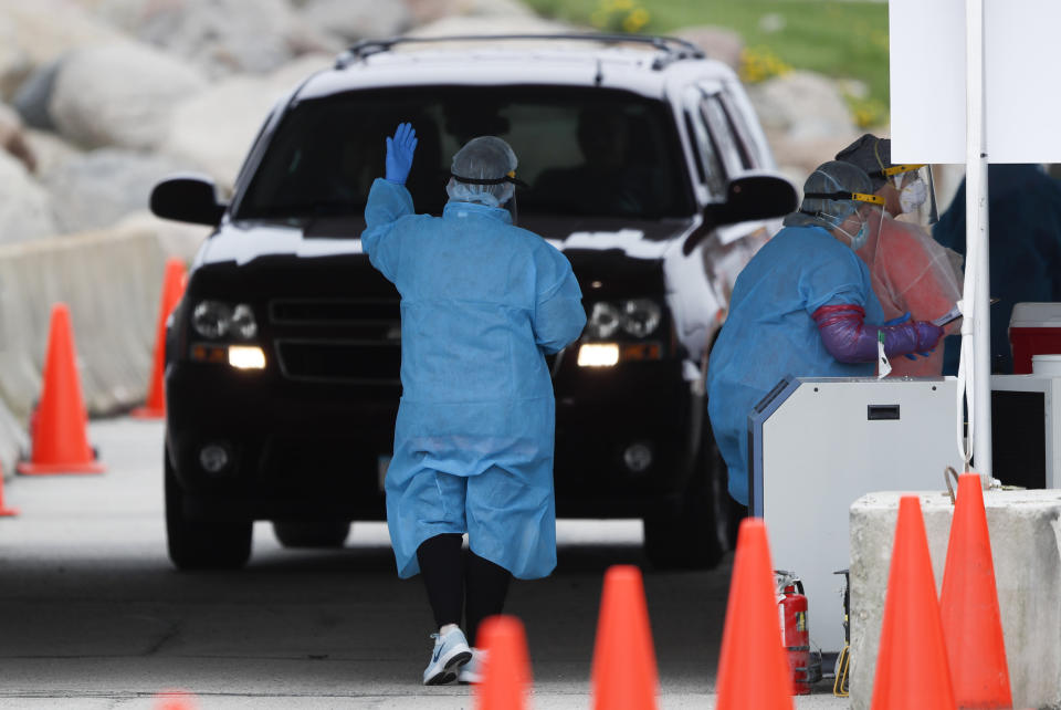 In this Friday, May 1, 2020, photo, a medical worker directs a local resident at a drive-thru COVID-19 testing site in Waterloo, Iowa. Local officials blame Tyson for endangering not only its workers and their relatives during the pandemic but everyone else who leaves home to work or get groceries. They are furious with the state and federal governments for failing to intervene — and for pushing hard to reopen the plant days after public pressure helped shut it down. (AP Photo/Charlie Neibergall)