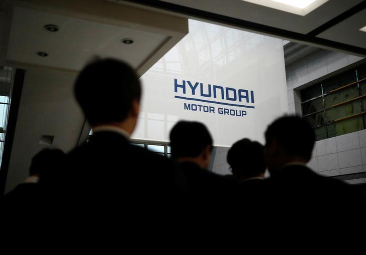 Employees of Hyundai Motor walk past the company's logo after the company's New Year ceremony in Seoul